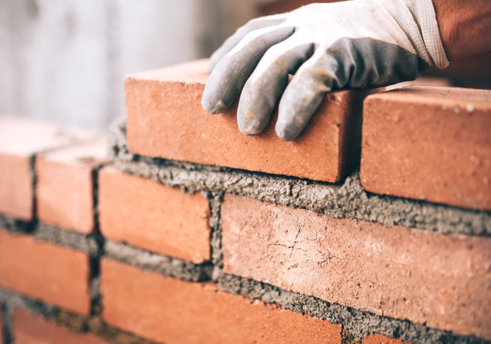 close-up-of-industrial-bricklayer-installing-P99HVE8